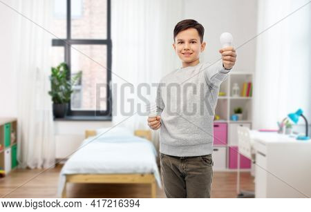 eco living and sustainability concept - smiling boy comparing energy saving light bulb with incandescent lamp over home room on background