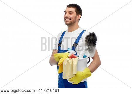 profession, service and people concept - happy smiling male worker or cleaner in overall and gloves with cleaning supplies over white background