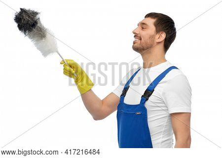 profession, cleaning service and people concept - happy smiling male worker or cleaner in overall and gloves with duster over white background