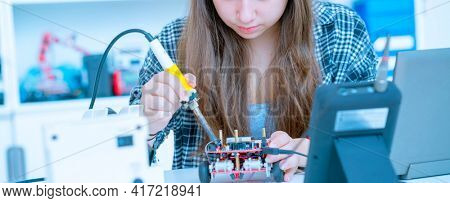 woman  technician with PCB electronic plate  in lab