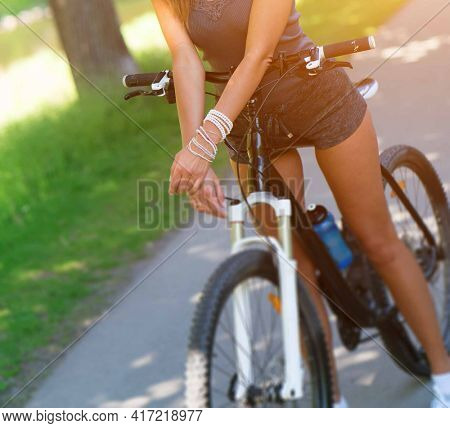 Young brunette woman in shorts and sunglasses riding a sport bike in a spring park