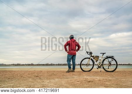 spring biking, touring or commuting - male cyclist with a bicycle on a lake beach, Boyd Lake State Park in northern Colorado