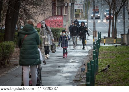 Belgrade, Serbia - March 6, 2021: Selective Blur On A Mother, Woman, And Her Daughter, Firl Walking