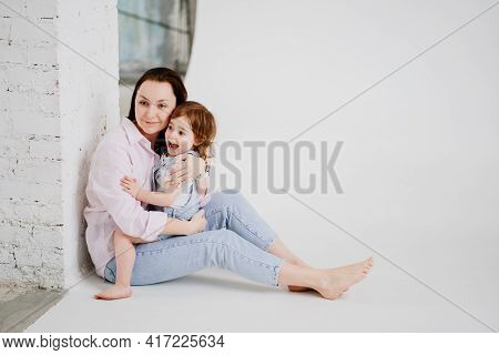 Beautiful Happy Family Sit On Floor And Cuddle In White Photo Studio. Backstage.