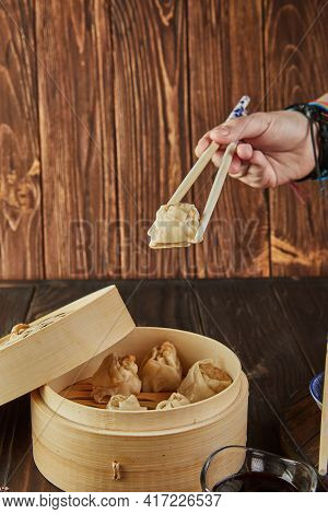 Shumai Shaomai Chinese Meat Dumplings Steamed In A Bamboo Steamer. Hand With Chopsticks Holding Dim
