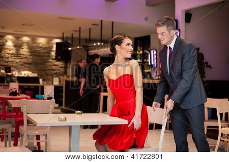 Young man abide chair to his girlfriend, gentlemen