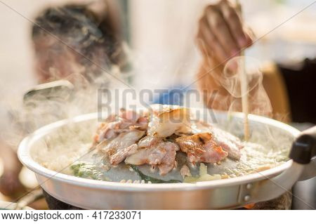 Closeup Image Of Thai Style Grilled Sliced Pork (thai Barbeque) On Stove Surround By Boiling Soup Wi