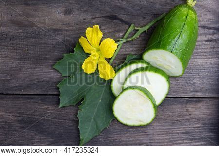 Fruit And Flower Of The Green Luffa That Is Used For Asian Cuisine, On Rustic Wooden Background