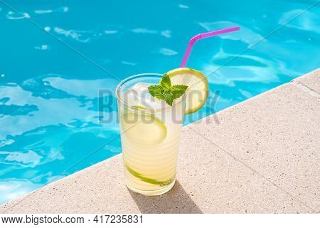 Fresh Lemonade Or Mojito Cocktail In Glass With Straw On A Swimming Poll Border On Sunny Day