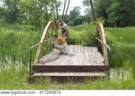 Urban Teenage Girls Came From Town To Village, Walk Along A Small Wooden Bridge In A Picturesque Par
