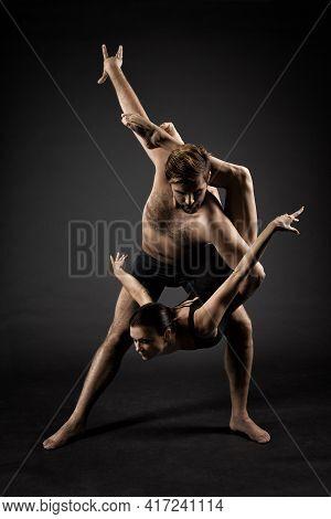 Ballet Dancers Over Black Background. Acrobatic Ballet Couple Dance