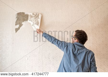 Caucasian Man Tearing Off Old Wallpaper From Wall Preparing For Home Redecoration