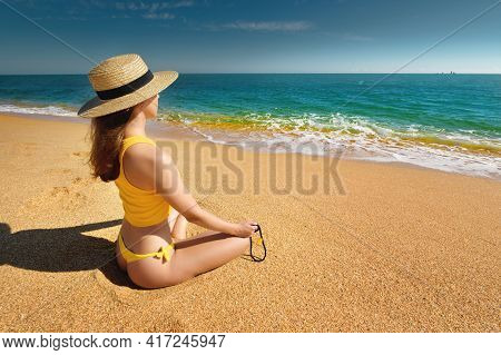 Young Caucasian Woman In A Swimsuit And A Tank Top Sits In A Lotus Position On The Sandy Seashore On