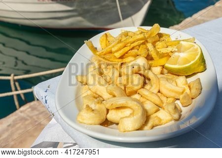 Grilled Fresh Squid On White Plate With Lemon And Chips. Traditional Mediterranean Dish, Tavern In N
