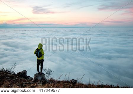Victory Of A Young Climber After Climbing A Mountain With A Backpack. View Of Floating Clouds And Su