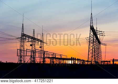 Electricity Poles At Sunset. High Voltage Grid Towers With Wire Cable At Distribution Station.