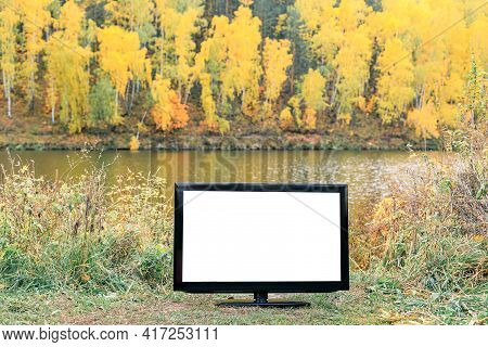 Tv With Blank Screen Mocap For Your Image On The Background Of The Autumn Forest By The River. Tv By