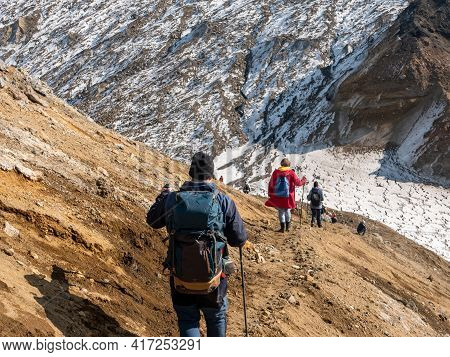 Descent Of Tourists From The Mutnovsky Volcano. Group Of Tourists Descends In Formation After Climbi