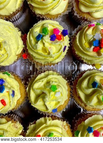 A Tray Of Yellow Icing Cupcakes With Red Green Blue And Yellow Sprinkles