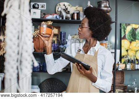 Side View Of Experienced Saleswoman In Eyeglasses Using Modern Tablet For Working And Checking The S