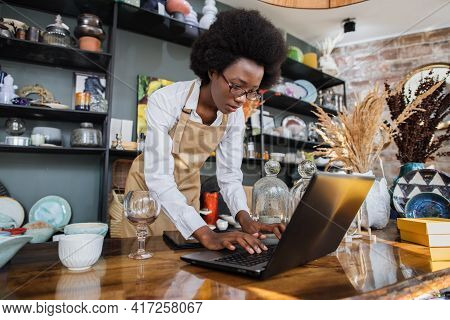 Young African Woman In Eyeglasses Doing Inventory At Decor Shop. Competent Saleswoman Using Modern L