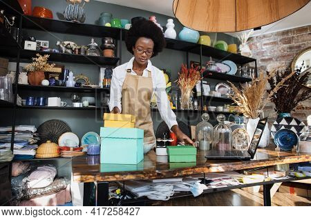 Qualified Afro American Saleswoman In Eyeglasses Packing Boxes With Various Souvenirs For Clients. B
