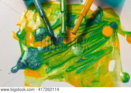 Bright Nail Polish In Green, Yellow, Blue Colors With Sparkles Spilled.