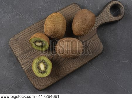 Wooden Desk With Ripe Kiwi Fruit Sliced On A Half , Close Up Image Of Ripe Juicy Kiwi Fruit For Heal