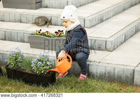 Mom And Daughter Spending Time Together In Front Or Backyard Of House, Planting Flowers, Girl Wateri