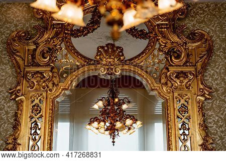 A Large Gold Chandelier With Patterns And Many Shades Is Reflected In A Large Antique Wall Mirror Wi