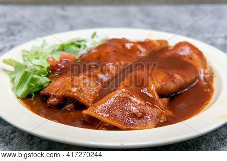 Chicken Enchiladas Smothered In Tasty Red Sauce On A Plate Makes For A Filling And Hearty Entree.