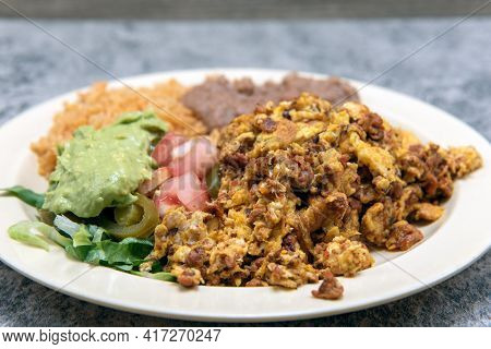 Hearty Plate Of Mexican Food Of Chorizo And Eggs Served With Refried Beans And Rice.