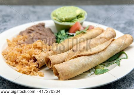 Tradional Comibination Plate Of Tasty Mexican Food Consisting Of Taquitos, Rice, And Refried Beans.