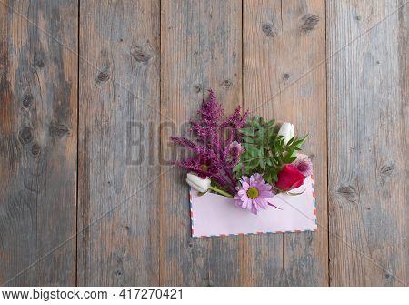 Spring Flowers Inside A Vintage Envelope On Wooden Background