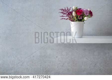 Assorted Flowers Design On Floating White Shelf Against Concrete Wall