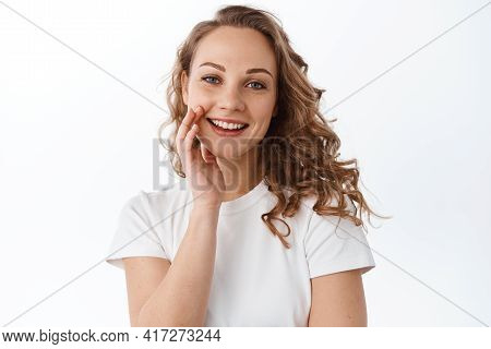 Beauty. Young Natural Blond Girl, Touching Clean Hydrated Face, Smile And Look Happy At Camera, Stan