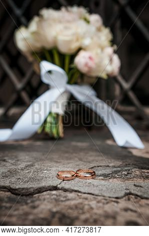 Wedding Gold Rings On The Background Of The Bride's Bouquet With Roses And Metal Lattice