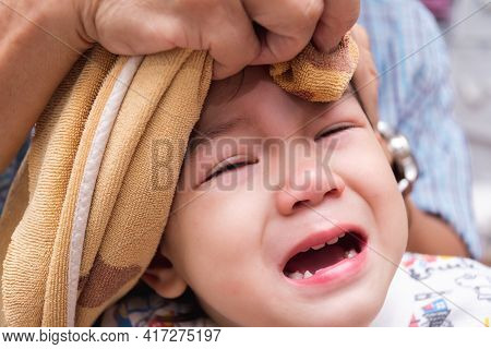 Boy Is Crying Out Of Pain. Child Bumps The Head Against Solid. Baby Is Bulging. Adult Is Wrapping Ic