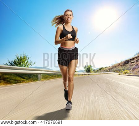 Full length portrait of a young female jogging outdoors on an open road