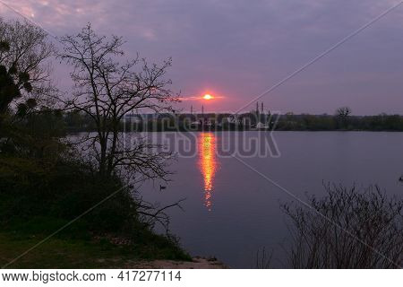 Dark Sunset Or Sunrise Over The Water. Dramatic Sky With Sundown On The Horizon. Silhouette Of Veget