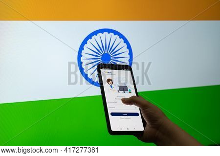 Man Woman Holding The Co-win Covid19 Coronavirus Vaccination Tracking App Against A Flag Of India As