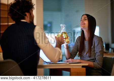A young sexy businesswoman enjoying a drink with a handsome businessman in a relaxed atmosphere at a date in an apartment. Business, date, relationship
