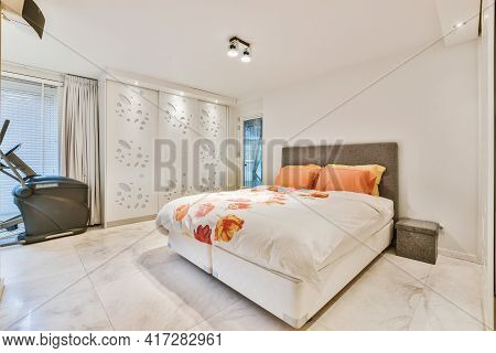 Queen Size Bed With Cozy Duvet In Light White Room With Marble Tiled Floor And Training Machine Near