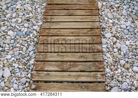 Wooden Walkway To Sea On Pebbles. Path On The Beach.