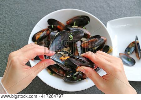 Closeup Hands Grabbing Mussel's Meat Out By Using An Empty Mussel Shell, With A Blurry Belgian Steam