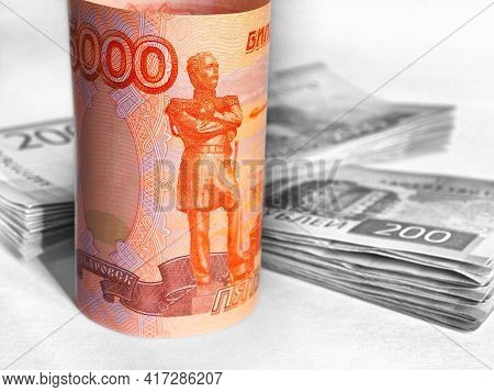 Brightly Lit Russian Banknote 5000 Rubles On A Dark Background. The Background Includes Stacks Of 20