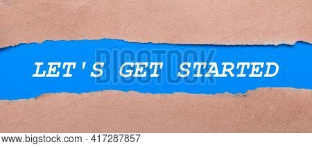 A Strip Of Blue Paper With The Words Let Is Get Started Between The Brown Paper. View From Above