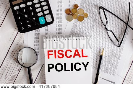 Fiscal Policy Written In A White Notepad Near A Calculator, Cash, Glasses, A Magnifying Glass And A