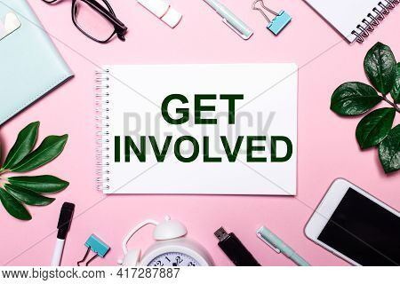 Get Involved Is Written In A White Notebook On A Pink Background Surrounded By Business Accessories