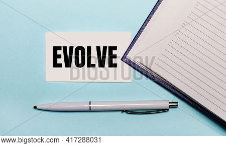 On A Light Blue Background, An Open Notebook, A White Pen And A Card With The Text Evolve. View From
